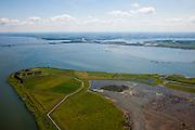 """Nederland, Zuid-Holland, Tiengemeten, 12-06-2009; eiland in het Haringvliet gezien naar het Oosten, Haringvlietbrug aan de horizon. .Oorspronkelijk gebruikt voor de akkerbouw maar inmiddels 'teruggegeven aan de natuur', de dijken zijn deels doorgestoken, de laatste boer is in 2006 vertrokken. Huidig gebruik onder andere zorgboerderij en kan er gekampeerd worden. De 'nieuwe natuur' vormt onderdeel van de Ecologische Hoofdstructuur. Oorspronkelijk was het eilandje eigendom van AMEV (Fortis Investments) - binnen de dijken, de buitendijkse slikken waren van de Vereniging Natuurmonumenten..The island Tiengemeten in the Haringvliet, originally owned - within the dikes - by AMEV (Fortis Investments), and Natuurmonumenten (Society for conservation of nature). The island was used for agriculture but has now """"been given back to nature"""", large parts have been flooded and the isle is part of the National Ecological Network. The last farmer left in 2006. Current use, among other, care farms and camping..Swart collectie, luchtfoto (25 procent toeslag); Swart Collection, aerial photo (additional fee required).foto Siebe Swart / photo Siebe Swart"""