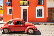 A red Volkswagen beetle passes a brightly painted orange building in Xico, Veracruz, Mexico.