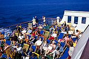 Passengers sitting in deckchairs of ferry ship deck enjoying sunshine, Sweden, 1970