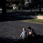 The family's small, rented home only has one 10'x12' room for the classroom. Jeanne, like most homeschoolers, utilizes all resources. Sidewalk chalk and the driveway become a chalkboard for Andrew learning to write his ABC's with help from Trevor.