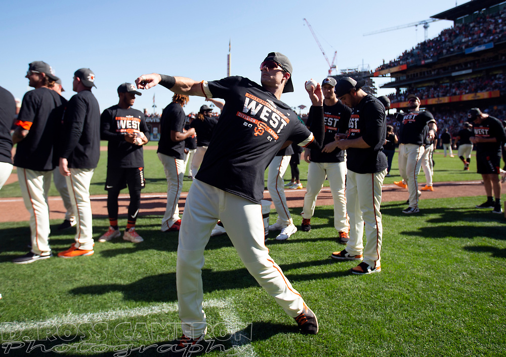 Oct 3, 2021; San Francisco, California, USA;  San Francisco Giants center fielder Mike Yastrzemski lobs baseballs to the fans in the stands as the team celebrates their 11-4 victory over the San Diego Padres at Oracle Park. The Giants clinched the National League West Division with the win. Mandatory Credit: D. Ross Cameron-USA TODAY Sports