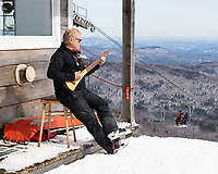Ski patroler catching some rays and playing guitar at the top of the sunny side double chair at Mad River Glen, Vermont, USA