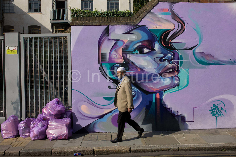 A Muslim man walks past street art on a wall near Brick Lane, London. The local man walks down the street passing bags of purple recycling bags which match the same colour of the urban mural - an artistic aerosol representation of a face. This is a scene of traditional Islamic culture living alongside a different ethnicity in the capital's eastern area, from the 1970s, a largely Bangladeshi community along Brick Lane. Today, it is the heart of the city's Bangladeshi-Sylheti community and is known to some as Banglatown.