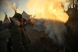 November 25, 2016 - Cannon Ball, North Dakota, U.S - DAVID OMONDI stands by a campfire during sunrise at the Oceti Sakowin Camp at the Standing Rock Indian Reservation in Cannon Ball, North Dakota. (Credit Image: © Joel Angel Ju‡Rez via ZUMA Wire)