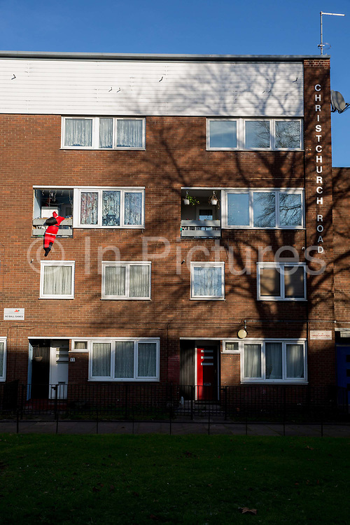 A fake Santa Claus hangs from a third story housing estate balcony on Christchurch Road on the 13th December 2018 in south London in the United Kingdom.