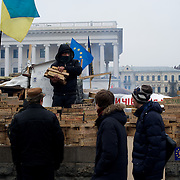 December 20, 2013 - Kiev, Ukraine: A pro-EU demonstrator builds a wall with wooden bricks printed with the names of every village and city who's population have representation in the month long protests at the Independence Square, also know as Maidan, in central Kiev.<br /> On the night of 21 November 2013, a wave of demonstrations and civil unrest began in Ukraine, when spontaneous protests erupted in the capital of Kiev as a response to the government's suspension of the preparations for signing an association and free trade agreement with the European Union. Anti-government protesters occupied Independence Square, also known as Maidan, demanding the resignation of President Viktor Yanukovych and accusing him of refusing the planned trade and political pact with the EU in favor of closer ties with Russia.<br /> After a days of demonstrations, an increasing number of people joined the protests. As a responses to a police crackdown on November 30, half a million people took the square. The protests are ongoing despite a heavy police presence in the city, regular sub-zero temperatures, and snow. (Paulo Nunes dos Santos/Polaris)