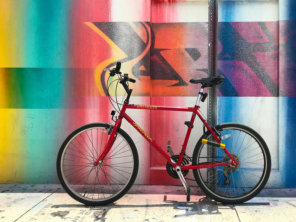 Red bike parked near a spray-painted mural in Miami's street art district.