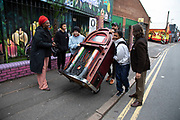 Friends laughing and havnf fun as they wheel a large jukebox along the street in Digberth, Birmingham, United Kingdom. Digbeth is an area of Central Birmingham, England. Following the destruction of the Inner Ring Road, Digbeth is now considered a district within Birmingham City Centre. As part of the Big City Plan, Digbeth is undergoing a large redevelopment scheme that will regenerate the old industrial buildings into apartments, retail premises, offices and arts facilities. There is still however much industrial activity in the south of the area.