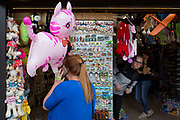 A lady shopper uses her phone while looking at tourist trinkets outside a Polish souvenir stall on Krupowki Street, on 16th September 2019, in Zakopane, Malopolska, Poland.
