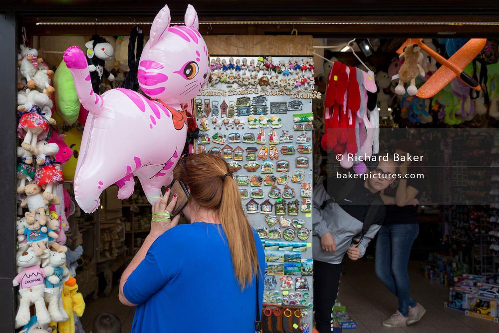 A lady shopper uses her phone while looking at tourist trinkets outside a Polish souvenir stall on Krupowki Street, on 16th September 2019, in Zakopane, Malopolska, Poland.