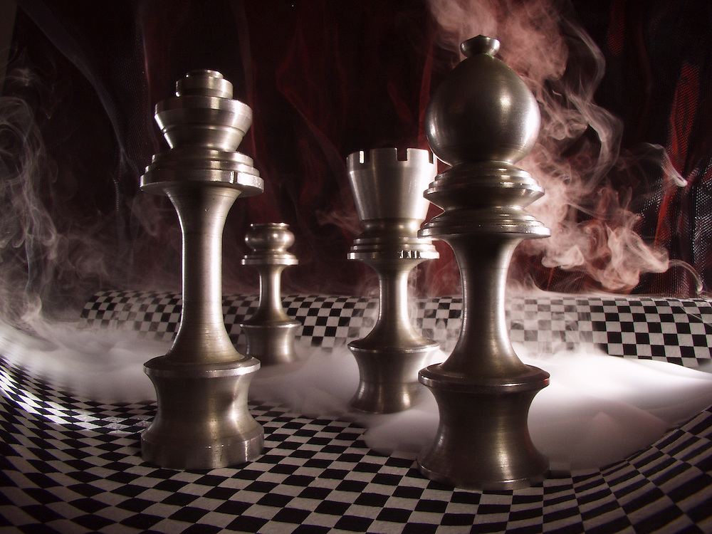 Chess pieces on a surreal playing board. Bringing to mind a little bit of Alice in Wonderland.
