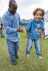 Father helping son to walk on stilts at a Parklife summer activities event,