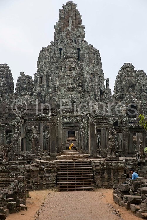 Bayon Temple which stands in the centre of the walled temple complex of Angkor Thom, Siem Reap Province, Cambodia, South East Asia.  The temple was built around 1190 AD by King Jayavarman VII as a Buddhist temple, but it incorporates elements of Hindu cosmology.  In the centre is a statue of Buddha with a yellow tunic.
