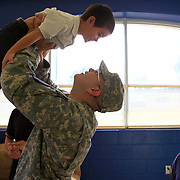 Spc. Daniel Overway lifts his younger brother Jose, 5, into the air as his sister Maria, 10, watches after he surprised them at Truman Elementary School in Edinburg. Overway recently returned to his home base in North Carolina from a 10 month tour with the U.S Army in Afghanistan and is spending Thanksgiving with his family in the valley. <br /> Nathan Lambrecht/The Monitor