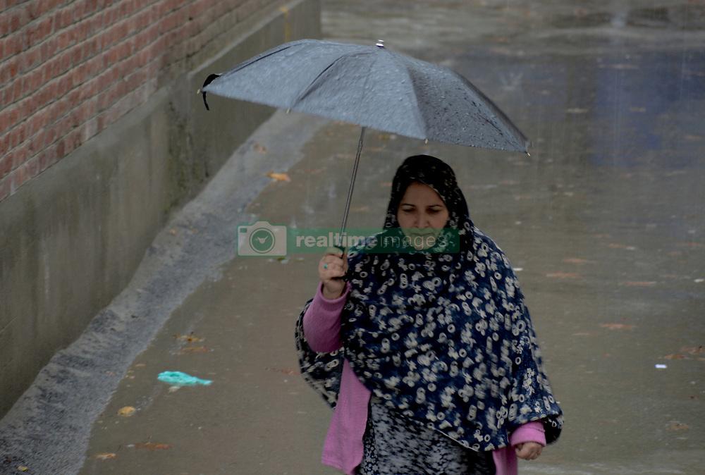 A Kashmiri woman walks holding umbrella amid rain and snow in Srinagar, the summer capital of Indian controlled Kashmir. Kashmir witnessed its first snowfall.