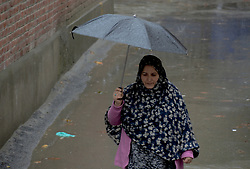 A Kashmiri woman walks holding umbrella amid rain and snow in Srinagar, the summer capital of Indian controlled Kashmir. Kashmir witnessed its first snowfall.