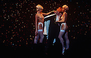 On stage, two beautiful topless girls stand semi-naked with a gentleman admirer during a variety show at the famous Parisian cabaret company Paradis Latin, Paris France. In front of glittery stars, the two ladies of the night are dressed in satin stockings and suspenders, flirting with this male dressed in top hat and tails, holding the hand of one lady and the about to kiss the cheek of the other, all the time lit with stage spotlights and the silhouetted heads of the front row audience at the bottom of the picture. The two girls appear to be twins but are probably wearing blonde wigs to make them look like a male 'Gentlemen prefer blondes' fantasy. (From a story about travelling through 6 European countries by coach in 7 days).