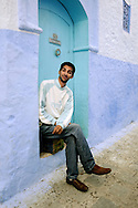 Morocco, Chefchaouen. Local man sitting at the blue door.