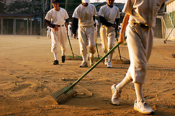 Japanese school baseball team raking sand on field after practice game