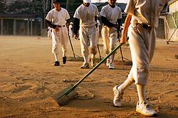 Japanese school baseball team raking sand on field after practice game