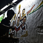 Brazilian artist Jambiero puts his final touches on the German team portion of his World Cup themed mural after Germany defeated Argentina 1-0 in the final of the World Cup on Copacabana Beach in Rio de Janeiro on Sunday, July 13, 2014. Credit: Byron Smith