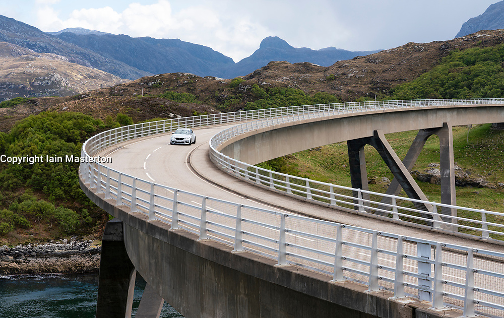 Car driving on the Kylesku Bridgeo on the North Coast 500 tourist motoring route in northern Scotland, UK