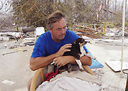 "Waveand Mississippi August 30, 2005, Brian Mollere hugs his mothers dog ""Rocky"" as search and rescue workers find him sitting alone on his concrete slab where their house used to be. Hurricane Katrina destroyed their home, the city of Waveland and Brian and Rocky were swept up in a 30ft wall of water and carrried over a half mile across the trian tracks. Brian had sent his mother to higher ground to ride out the storm but he decieded to stay and protect her home, the house was completely destroyed and his mother died in the storm ,she was in Bay St. Louis about 10 miles from her home.©SUZI ALTMAN PHOTOGRAPHER www.suzisnaps.com .cell phone 601-668-9611.ONE TIME USE ONLY-FOR MISSISSIPPI RISING GALA OCT.1,2005. SLIDE SHOW ONLY-NO PRINTS NO WEB NO DISTRIBUTION. (Photo/Suzi Altman)hurricane katrina, natural disatsters, mississippi gulf coast,(Photo/© Suzi Altman)hurricane katrina, natural disatsters, mississippi gulf coast,(Photo/© Suzi Altman)"