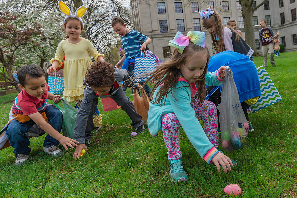Addison Dodson, 5, and other kindergartners of  Central Elementary School scramble for easter eggs filled with candy on the grounds of the Capitol Complex in Charleston, W.Va., on Tuesday, April 09, 2019.