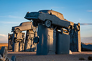 """Carhenge Sunset. Carhenge replicates England's Stonehenge using vintage American automobiles, near Alliance, Nebraska, in the High Plains region, USA. After studying Stonehenge in England, years later, Jim Reinders recreated the physical size and placement of Stonehenge's standing stones in summer 1987, helped by 35 family members. Reinders said, """"It took a lot of blood, sweat, and beers."""" Carhenge was built as a memorial to Reinders' father. 39 automobiles were arranged in the same proportions as Stonehenge with the circle measuring a slightly smaller 96 feet (29m) in diameter. Some autos are held upright in pits five feet deep, trunk end down, while other cars are placed to form the arches and welded in place. All are covered with gray spray paint. The heel stone is a 1962 Cadillac. Reinders donated Carhenge to the Friends of Carhenge, who gifted it to the Citizens of Alliance in 2013. Additional sculptures have been erected in the Car Art Reserve, where Reinders' """"Ford Seasons"""" is comprised of four Fords, inspired by Vivaldi's Four Seasons. Also, 29-year-old Canadian Geoff Sandhurst sculpted a spawning salmon."""