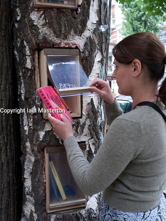 Woman borrowing a book from the Book Forest or Bucherwald where books are made available for swapping and borrowing for free on the streets of Prenzlauer Berg in Berlin