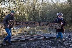 Harefield, UK. 18 January, 2020. Activists from Extinction Rebellion, Stop HS2 and Save the Colne Valley reoccupy Colne Valley wildlife protection camp from which all but two activists had been evicted by enforcement agents acting for HS2 the previous week during the second day of a three-day 'Stand for the Trees' protest in the Colne Valley timed to coincide with tree felling work by HS2. 108 ancient woodlands are set to be destroyed by the high-speed rail link.