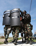 Members of the Layton City Police SWAT team back away from a home after delivering a phone to be used for negotiations during a hostage training scenario April 11, 2003. Units from the respective municipalities spent the day training in homes owned by Layton that are going to be demolished.                  .