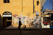 A local woman passes a graffiti-daubed street corner and tourist kiosk near Florence's Piazza Santa Croce. The smartly-dresses young lady walks by the ramshackle shop piled with souvenirs and trinkets, a rather untidy and unsafe-looking electricity junction box and a shop called The Gold Corner selling 18Kt gold. It is a bright morning and the sunshine illuminates the yellow wall that has been covered at ground level by the scrawls of graffiti by local youths - a facet of every corner of the city's medieval architecture.
