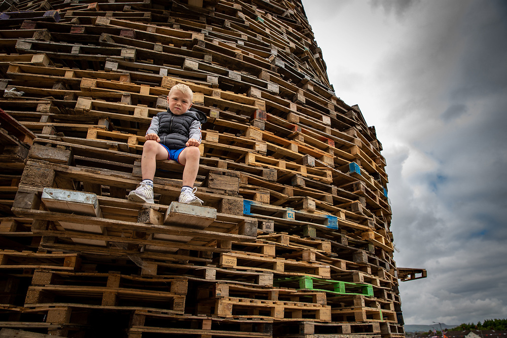 Young boy sits at the base of a huge bonfire in Larne, all ready for the midnight festivities to begin. Belfast, NI, 2021.