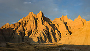Golden sunset illuminates layers of ancient sediments on the Loop Road near the Interior Entrance of Badlands National Park, South Dakota, USA. This park has the largest undisturbed mixed grass prairie in the United States. This image was stitched from multiple overlapping photos.