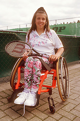 Teenage girl with disability; who is wheelchair user; holding tennis racket smiling,