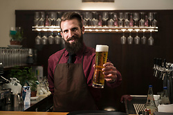 Portrait of young man offering glass of beer