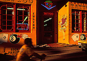 Image of a tattoo and body piercing storefront with boy on bike and yellow chevrolet outside, Manayunk, Pennsylvania, American Northeast by Andrea Wells