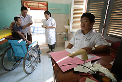 Staff members assist Laan 18, years old who was seriously injured when a UXO item exploded.  He lost one leg and a hand, plus the sight in both eyes, in the explosion. The COPE centre assists many people who have lost limbs due to UXO accidents. Pakse, Lao PDR.