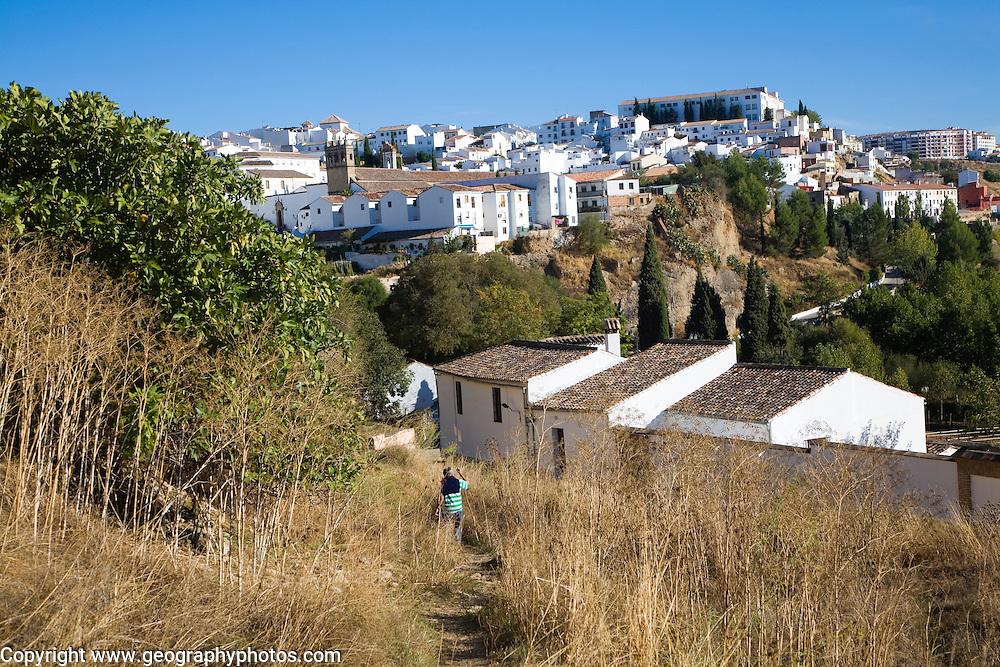 Man walking down path towards white buildings in newer area of Ronda, Spain