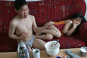 (MODEL RELEASED IMAGE). At breakfast, Emil's 10-year-old nephew Julian, who is visiting for a week, plays air guitar and eats sugar-drenched muesli while watching MTV in the Madsens' living room. Sleepily curled on the couch, his cousin Belissa ponders the antics of the rock stars while waiting for her mother to serve breakfast. Hungry Planet: What the World Eats (p. 155).