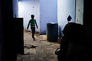 A boy delivers tea through an alleyway by Sitaram Bazar, Old Delhi, India
