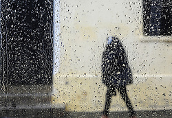 South Africa - Cape Town - 25 September 2020 - A woman covers her head with a blanket as she walks through the rain in the CBD. Capetonians are experiencing cold and wet weather as another cold front moves over the peninsula. Western Cape Dams are filling up quickly as most dams are reaching their full capacity. Picture: Henk Kruger/African News Agency(ANA).