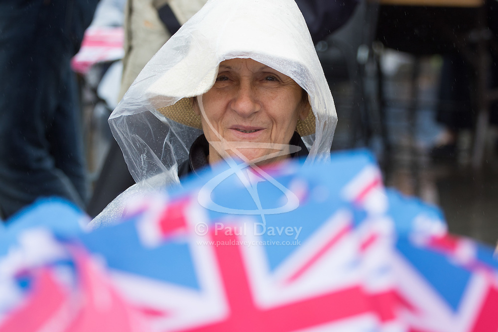 Trafalgar Square, London, June 12th 2016. Rain greets Londoners and visitors to the capital's Trafalgar Square as the Mayor hosts a Patron's Lunch in celebration of The Queen's 90th birthday. PICTURED: A woman watches the performances on the giant screen.