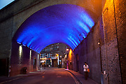 Lit up blue, a railway arch in Borough London.