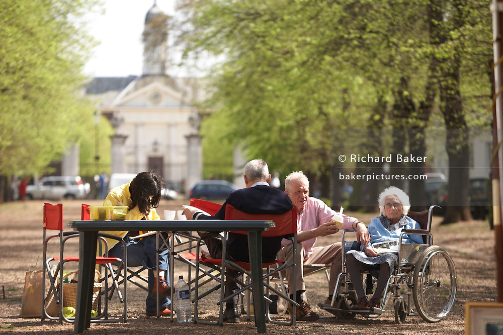 Elderly lady is looked after by family on sunny afternoon in Chelsea's leafy Royal Avenue SW3 with Chelsea Hospital in distance