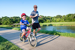 Jogger and boy on bike on the Trinity Trails near the Trinity River, Fort Worth, Texas, USA.