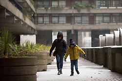 ©️ Licensed to London News Pictures. 08/02/2021. London,UK. Members of the public walk through Barbican Centre in central London during a snow shower in Bank, central East London. Snow is expected for large parts of the UK and a yellow weather warning is in place in parts of England as Storm Darcy hits the UK. Photo credit: Marcin Nowak/LNP