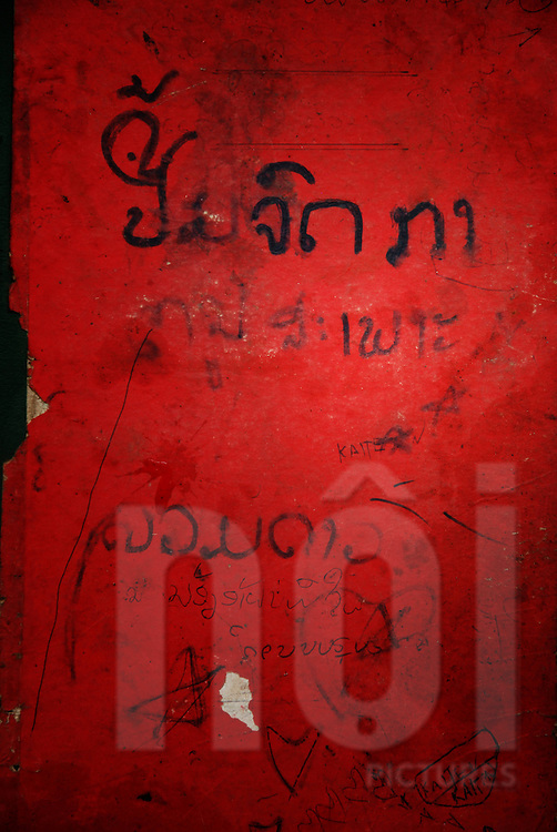 Laos writes in black ink on red wall in the abandoned cinema of Bouasavanh, Vientiane, Laos, Asia