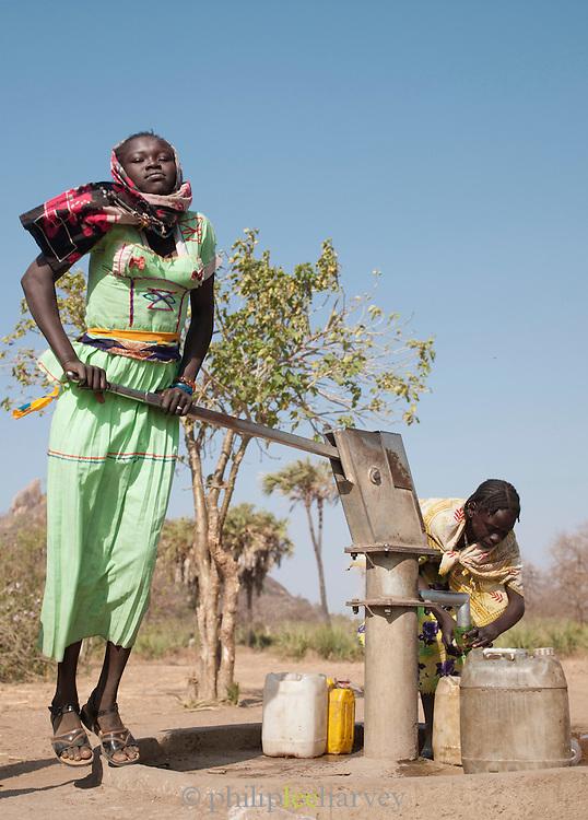 Girls of the Nuba tribe pumping water from a well in the village of Nyaro, Kordofan region, Sudan